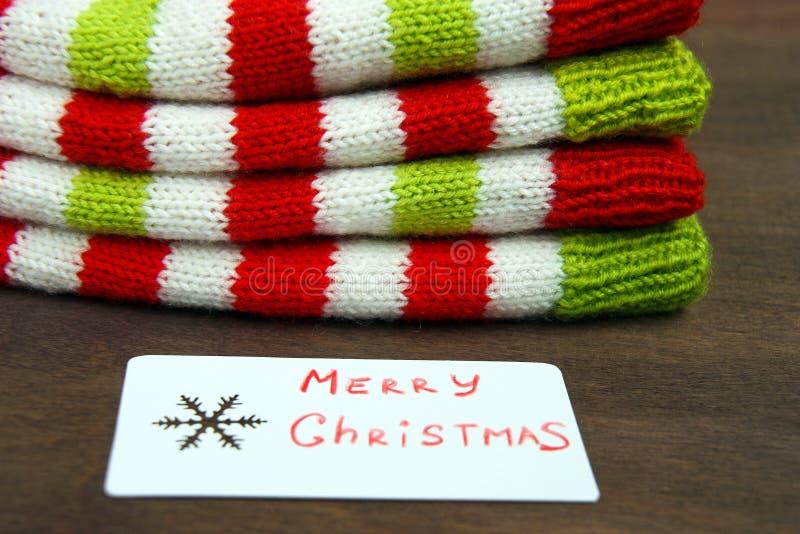 Röd färgrik jul, vit och gräsplan stack modeller av den Santa Claus hjälpredahatten, naturlig ull, handgjort stuckit, med pappers royaltyfri foto