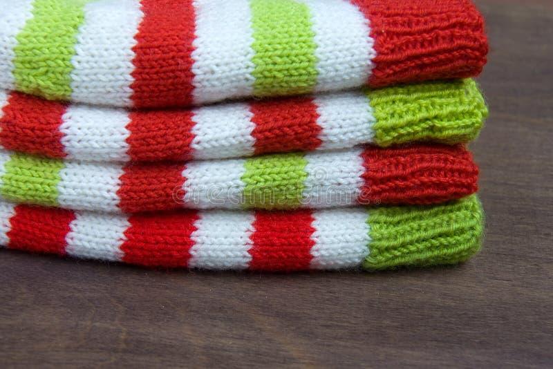 Röd färgrik jul, vit och gräsplan stack modeller av den Santa Claus hjälpredahatten, naturlig ull, handgjort stuckit, med pappers royaltyfri bild