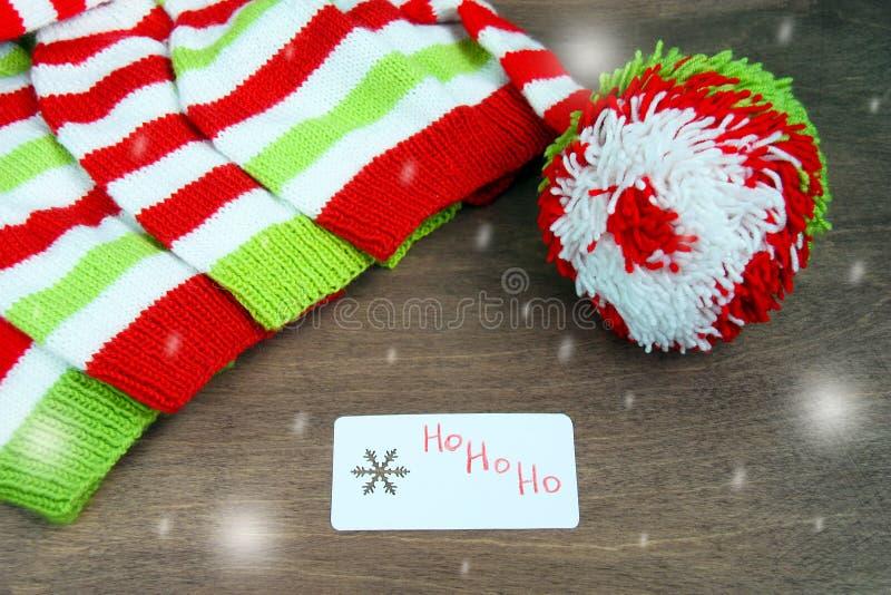Röd färgrik jul, vit och gräsplan stack modeller av den Santa Claus hjälpredahatten, naturlig ull, handgjort stuckit, med pappers arkivbild