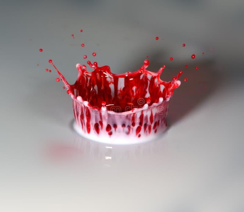 Röd färgstänk in i mjölkar arkivbild