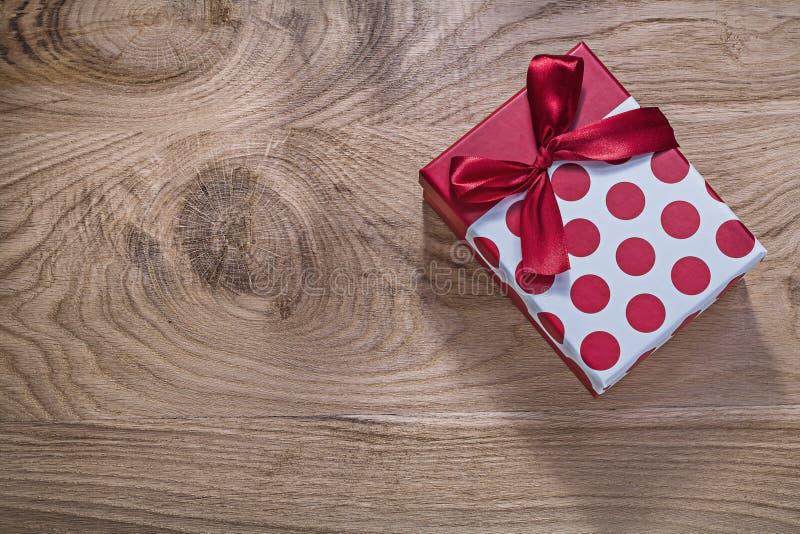 Röd födelsedaggåva på träbrädeberömbegrepp arkivbild