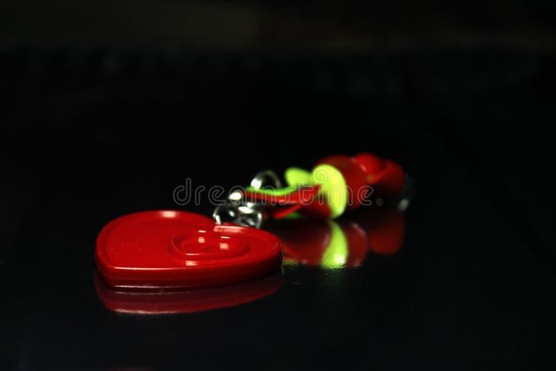 Röd förälskelse Keychain på svarta den Spacial bakgrundsvalentindagen arkivfoton
