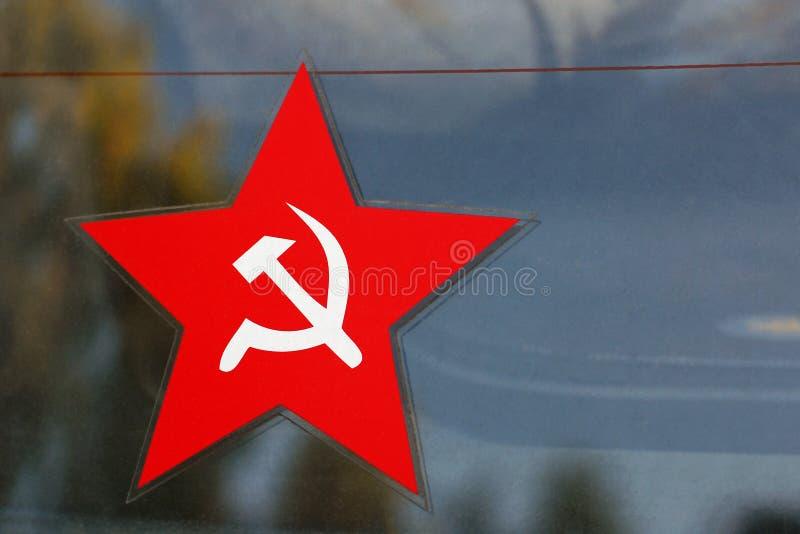 Röd fem-pekad stjärna med skära- och hammareemblemet arkivbilder