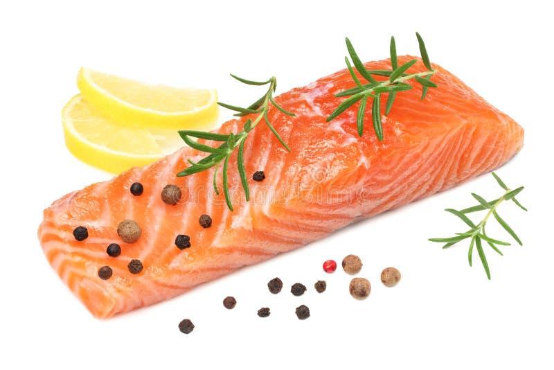 Röd fisk Rå laxfilé med rosmarin- och citronisolaten på vit bakgrund arkivfoto