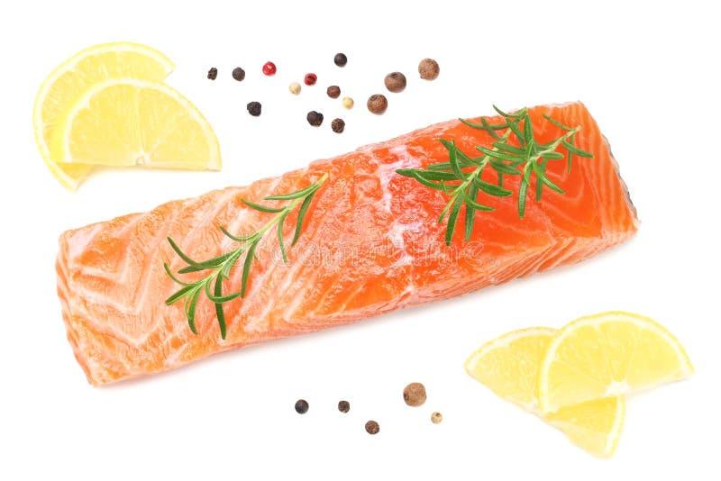 Röd fisk Rå laxfilé med rosmarin- och citronisolaten på vit bakgrund Top beskådar royaltyfri fotografi