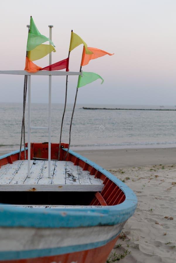 Röd fiskebåt med den färgrika flaggan i morgonen royaltyfria bilder