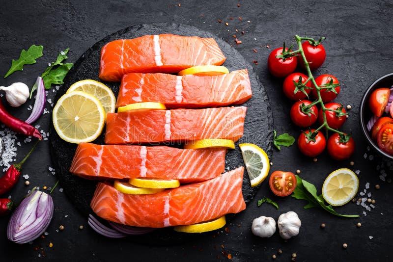 Röd fiskfilé för ny rå lax på svart bakgrund arkivbild