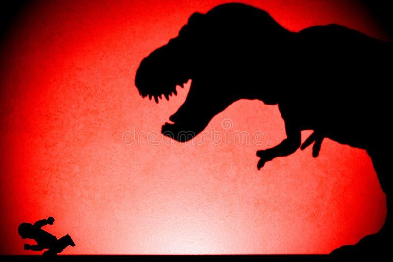Röd fläckljusskugga av tyrannosarien som jagar människan på väggen arkivbilder