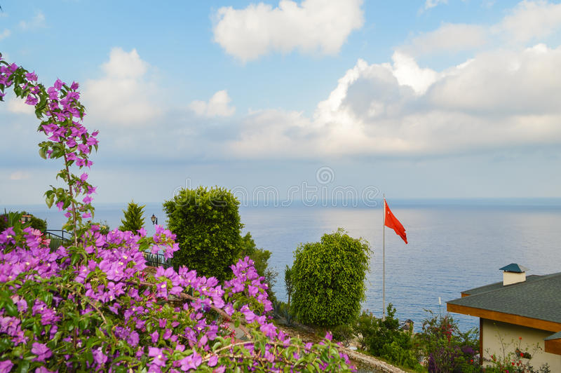 Röd flagga på bakgrunden av havet i Turkiet arkivbild
