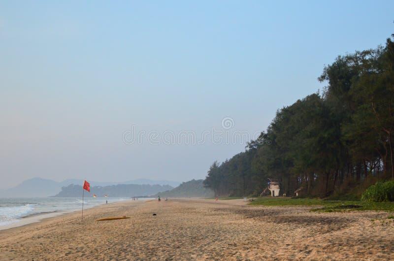 Röd flagga på den tomma stranden arkivbilder