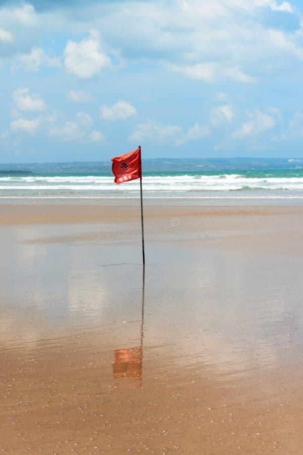 Röd flagga på strand med inga simninganmärkningar. arkivbild