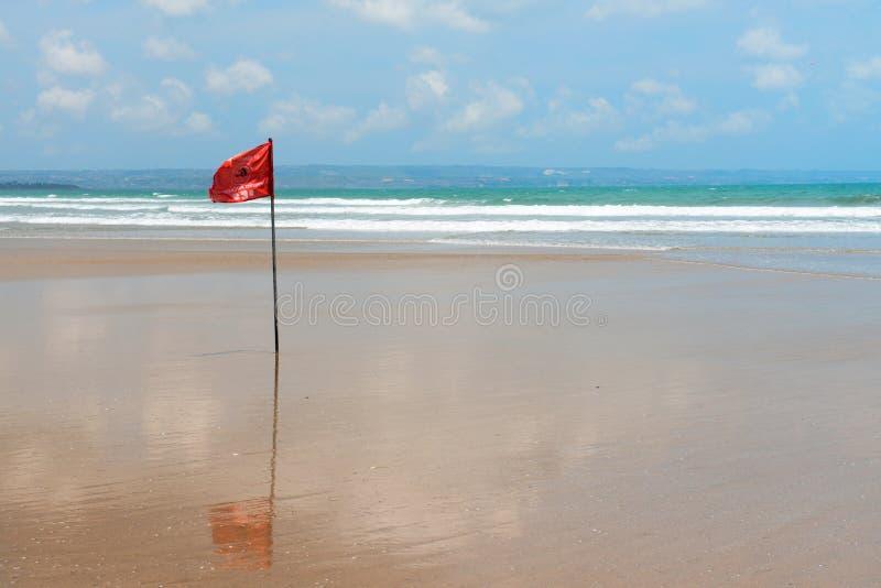 Röd flagga på strand med inga simninganmärkningar. royaltyfria bilder