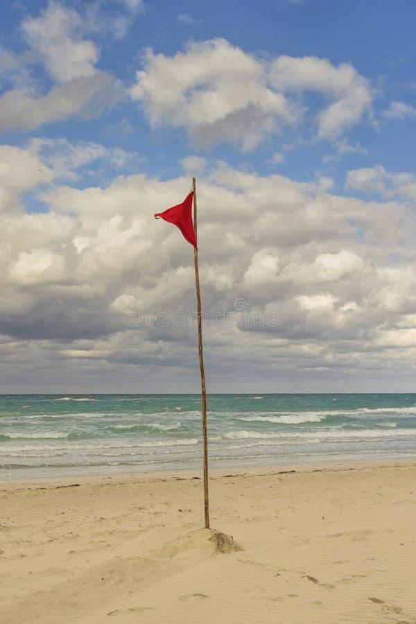 Röd flagga på stranden som förbjuder badning och skriver in vattnet royaltyfri fotografi