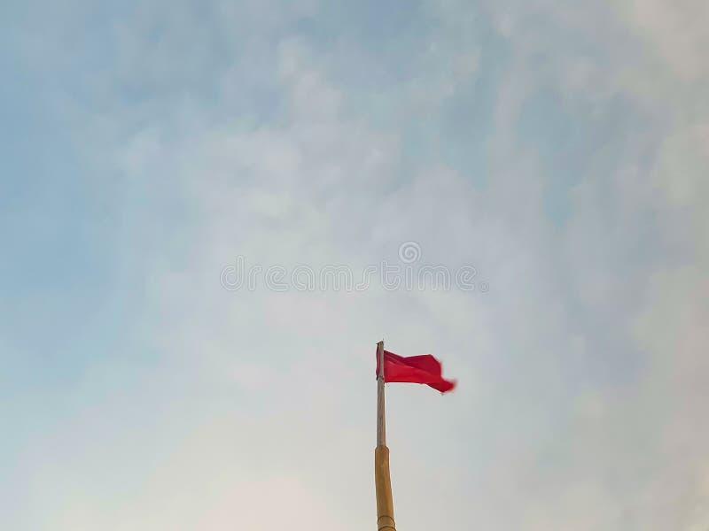 Röd flagga som blåser i vinden från en bambupol i himlen arkivfoton