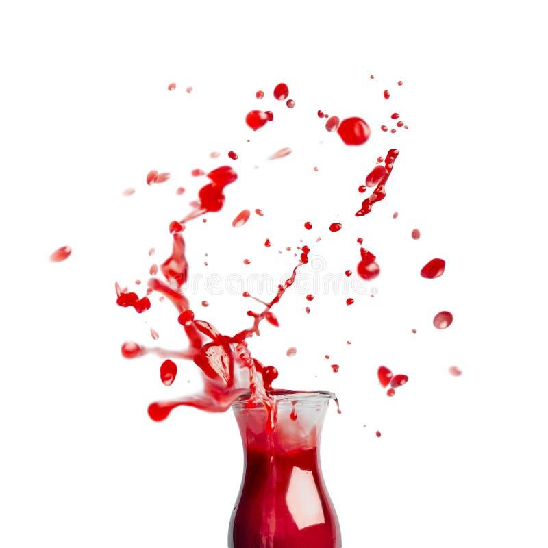 Röd fruktsaft- eller smoothieglasflaska med färgstänk som isoleras på vit bakgrund, främre sikt royaltyfria foton
