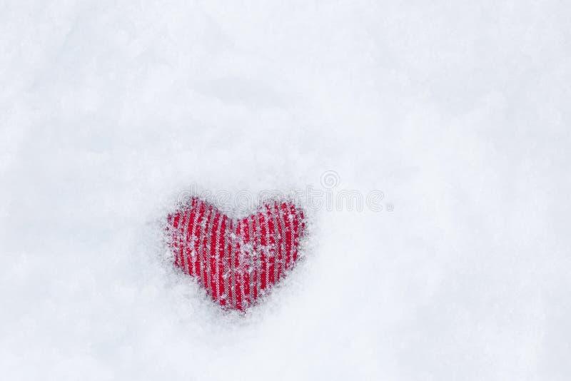 Röd fryst tyghjärta på vit snö med snöflingan på, snöig b royaltyfria bilder