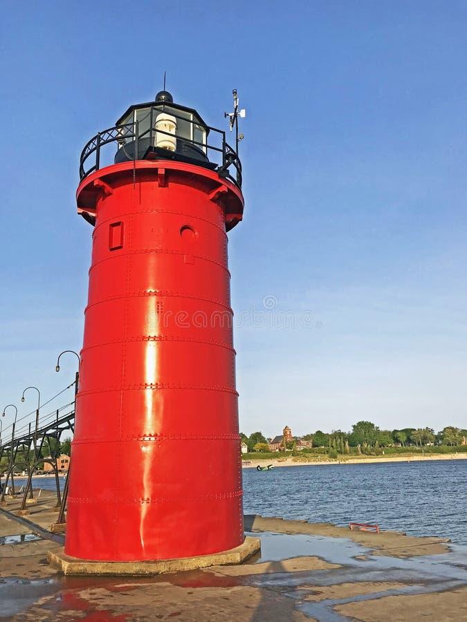 Röd fyr på ingången av den södra tillflyktsorthamnen arkivfoto