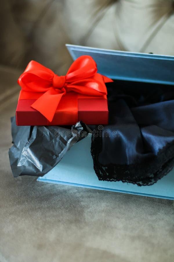 Röd gåvaask för lyxig ferie med den siden- band- och pilbåge-, jul- eller valentindagdekoren fotografering för bildbyråer