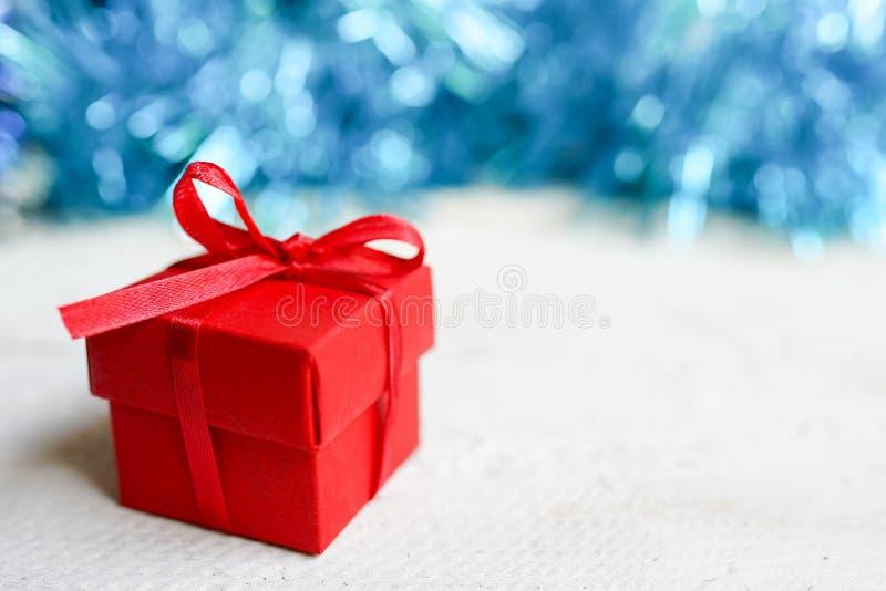 Röd gåvaask för nytt år på vit bakgrund med blå bokeh, kopieringsutrymme kortjul som greeting arkivfoton
