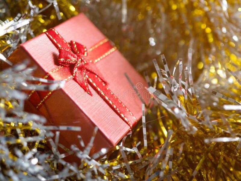 Röd gåvaask med den röda bandpilbågen och guld- sömsställe på glödande garnering för silver- och guldregnbåge nytt år för jul arkivfoto