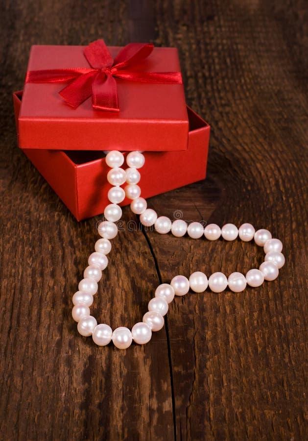 Röd gåvaask med en pärlemorfärg halsband i formen av hjärta royaltyfri fotografi