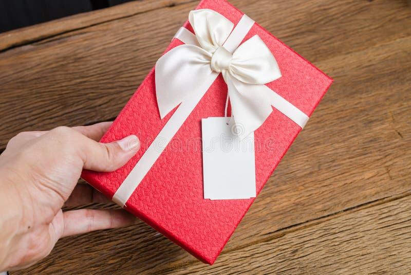 Röd gåvaask med etiketten royaltyfri fotografi