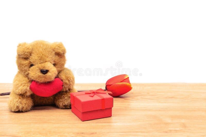 Röd gåvaask med tulpan och nallebjörnen på trätabellen royaltyfri fotografi