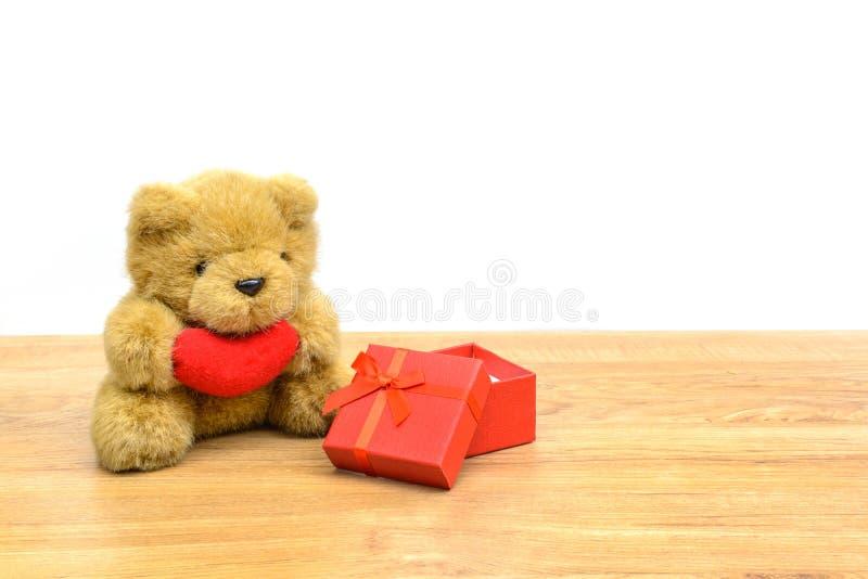 Röd gåvaask och nallebjörn på trätabellen fotografering för bildbyråer
