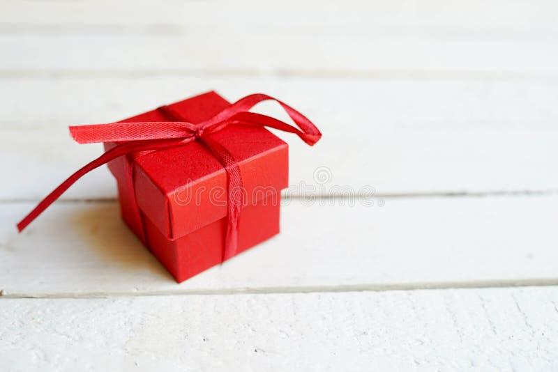 Röd gåvaask på vit träbakgrund med kopieringsutrymme, överraskningen för födelsedag, jul eller valentin dag arkivfoton