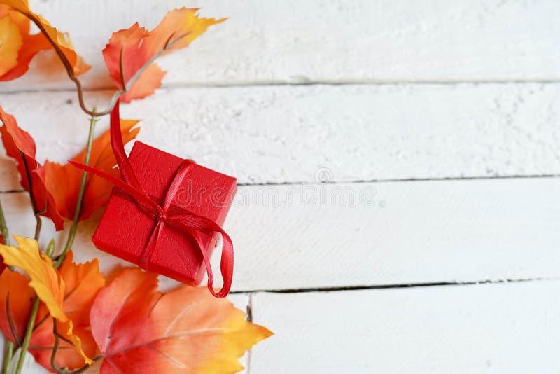 Röd gåvaask på vita åldriga träbräden med sidor för en höst, kopieringsutrymme royaltyfri foto