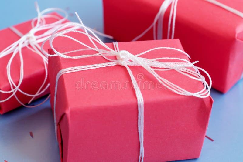 Röd gåvaboxesclose upp på blå bakgrund fotografering för bildbyråer