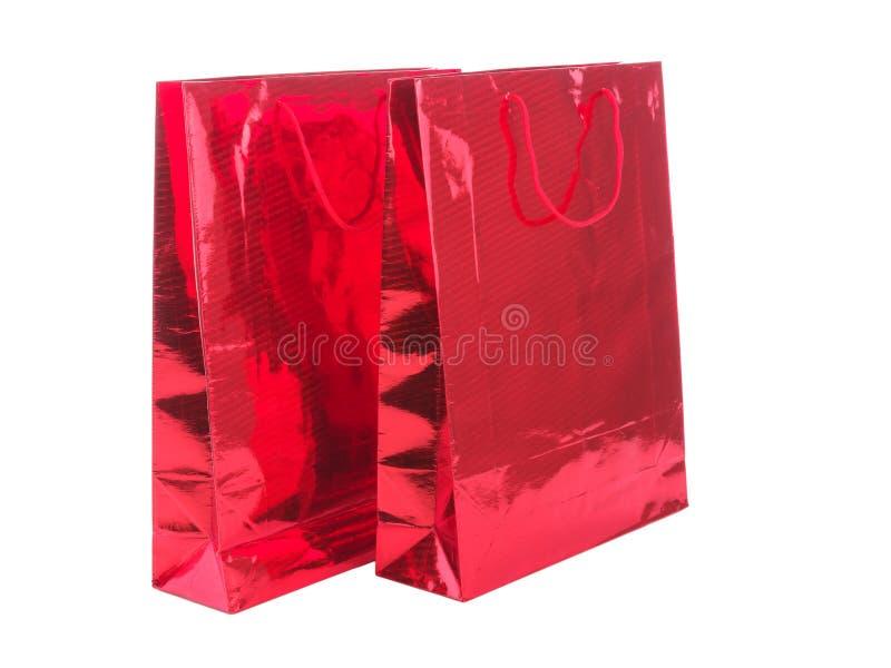 RÖD GÅVAPACKE PÅ VIT BAKGRUND Färgglade pappers- shoppingpåsar som isoleras på vit royaltyfri foto