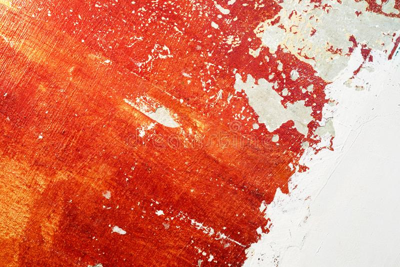 Röd gammal betongvägg med skalning av målarfärg och av ny murbruk royaltyfri foto