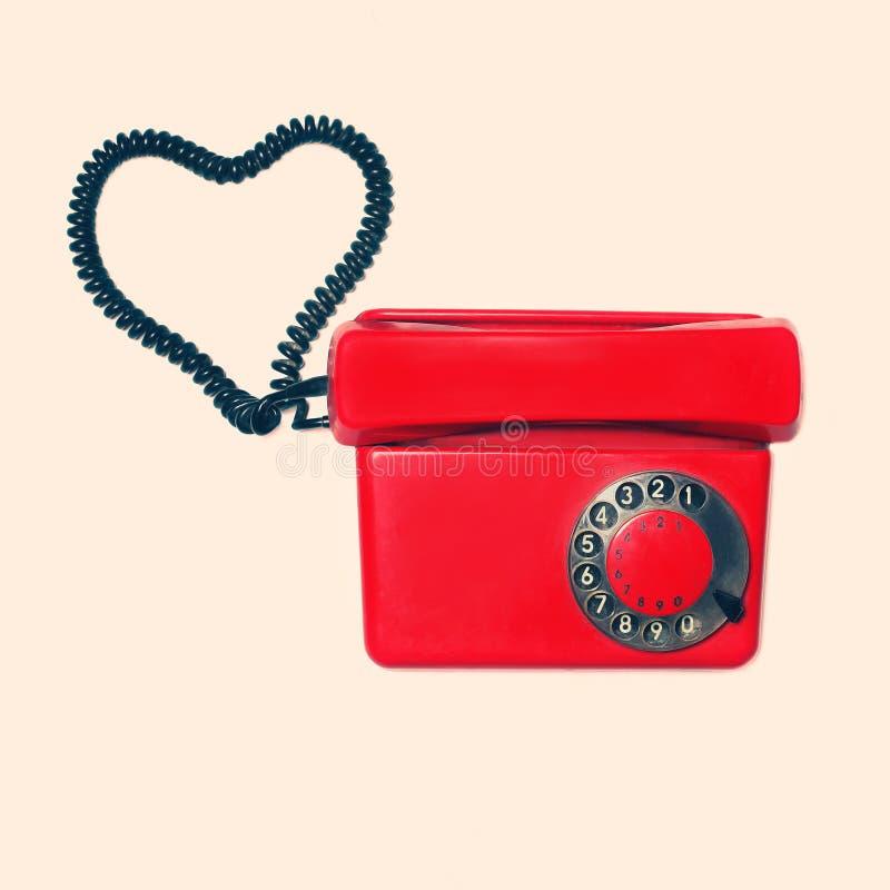 Röd gammal retro roterande telefon med hjärtaform av tråd, tappning arkivbilder