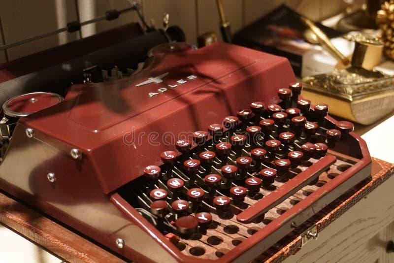 Röd gammal retro tappningantikvitetskrivmaskin arkivfoto