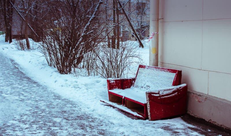 Röd gammal soffa som täckas med snö, ensamhet arkivfoton