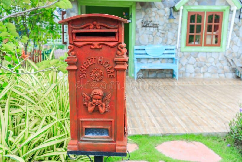 Röd gammalmodig brevlåda- eller tappningstolpeask framme av huset arkivfoto