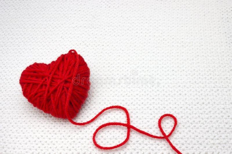 Röd garnboll som en hjärta på den vita virkningbakgrunden Romantiskt valentindagbegrepp Röd hjärta som göras av ullgarn med plac arkivfoton