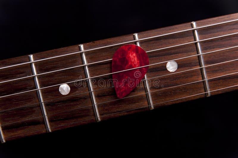 Röd gitarrhacka på fingerboarden arkivfoto