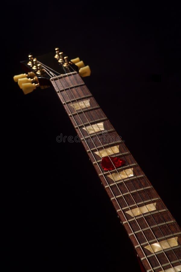 Röd gitarrhacka på fingerboarden och mörkret royaltyfri foto