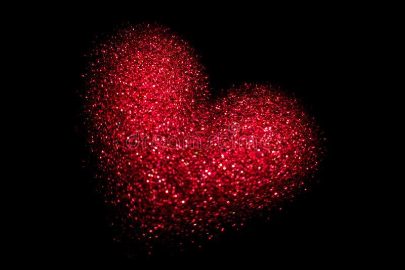 Röd glödande hjärta på en svart bakgrund lycklig s valentin för dag arkivfoto