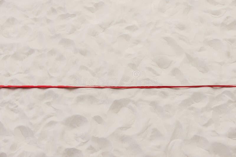 Röd gränslinje i strandvolleyboll Texturerad sand arkivbild