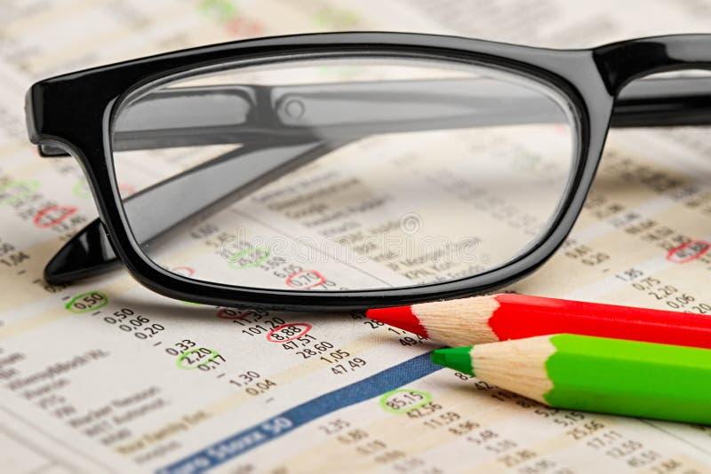 Röd grön pennblyertspenna för exponeringsglas på tidningen med bakgrund för affärsidé för finans för diagram för aktiemarknadutby arkivbilder