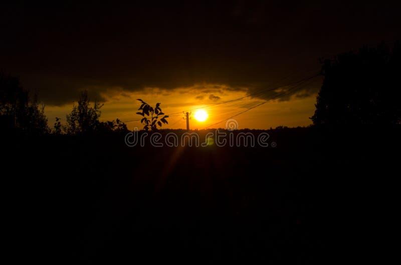 Röd gul solnedgång bak horisonten arkivbilder