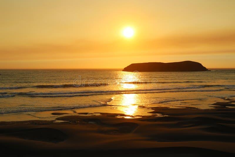 Röd guld Strålar av resningsolen över havet Den sandiga stranden har orange färg royaltyfria foton