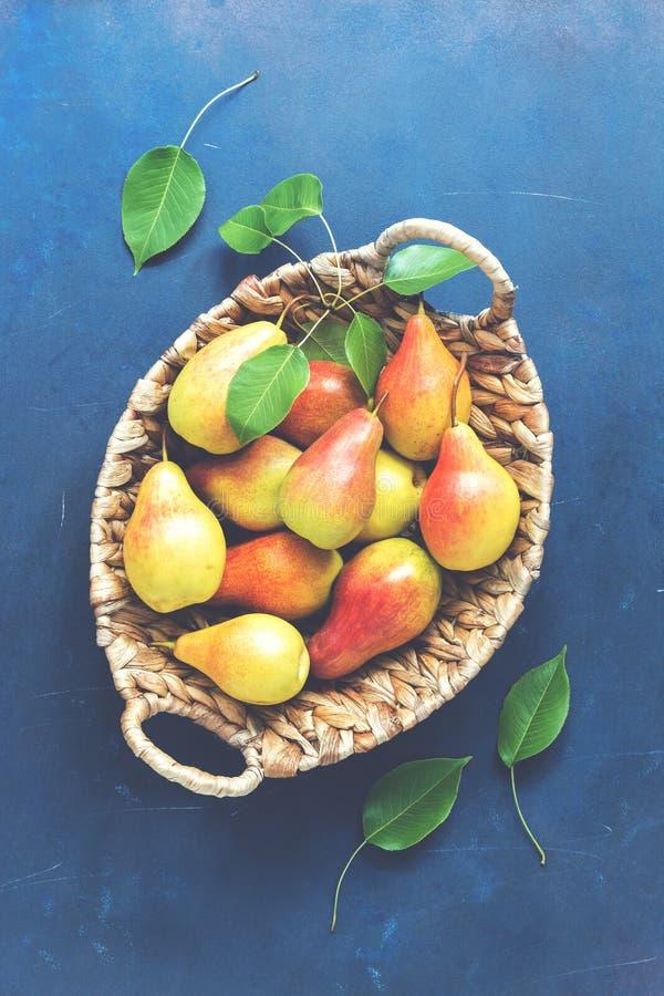 Röd-guling päron i en korg på en blå lantlig bakgrund Bästa sikt, tonat foto royaltyfri foto