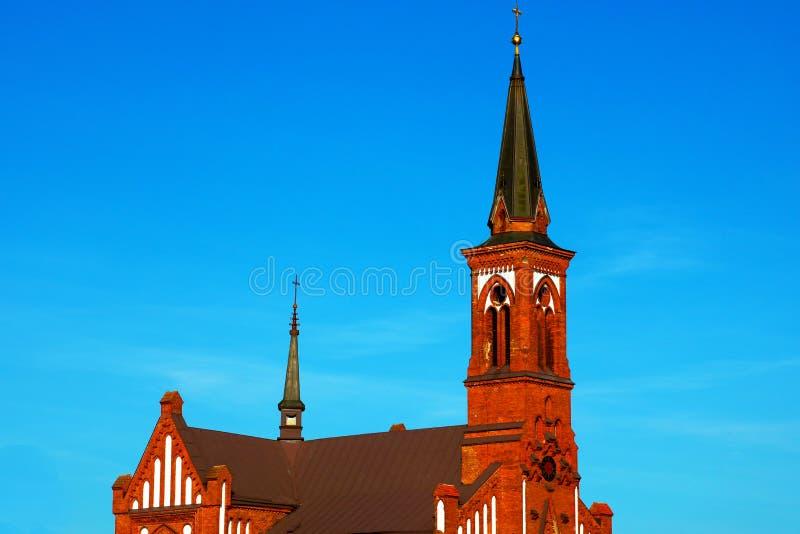 Röd härlig kyrka på en bakgrund av blå himmel på en solig dag royaltyfri bild