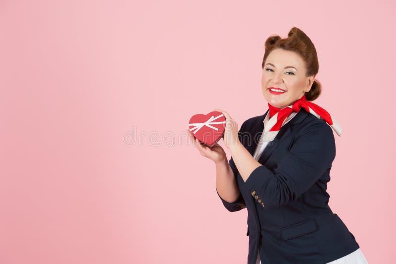 Röd hårstewardess i enhetlig framlägga ask med bandet Brunettkvinna med röd hjärta i hand på rosa bakgrund royaltyfri bild
