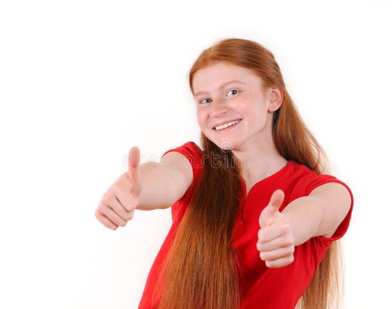 Röd hårtonåringflicka i röd en skjortauppvisning tummar-upp på båda händer royaltyfria bilder