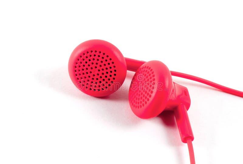 Röd hörlurcloseup på vit royaltyfria bilder